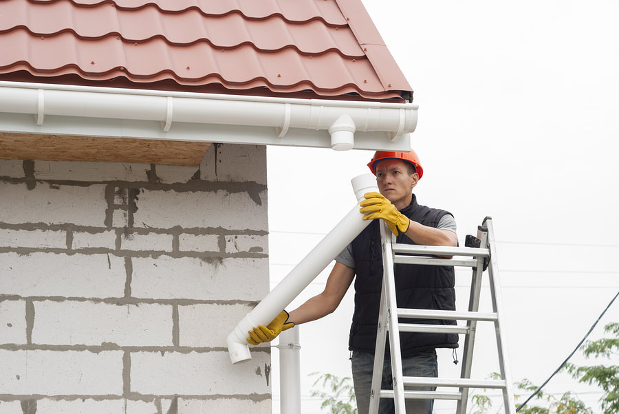 man working at the top of the house
